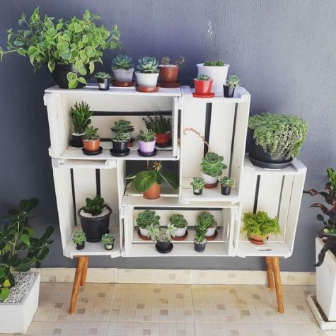 a simple and chic garden made of crates and wooden legs is a cute idea of an open storage unit