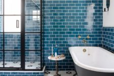 23 bright teal tiles on the wall are accented with white grout, and a hex tile floor adds interest