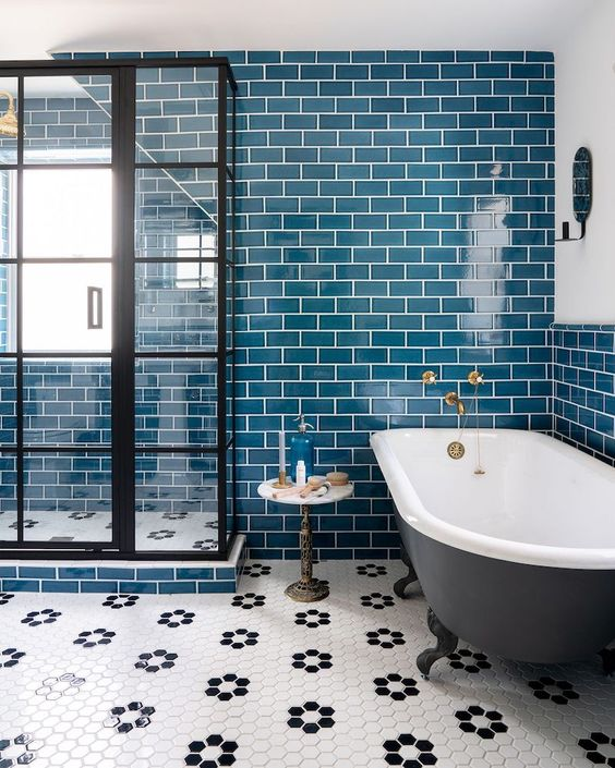 bright teal tiles on the wall are accented with white grout, and a hex tile floor adds interest