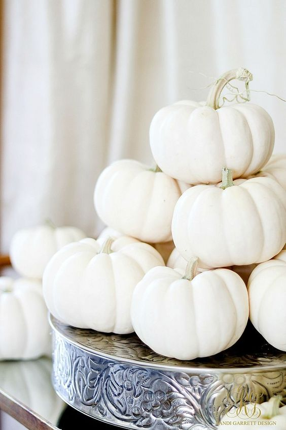 a glam fall arrangement of a vintage metal holder and a stack of white pumpkins
