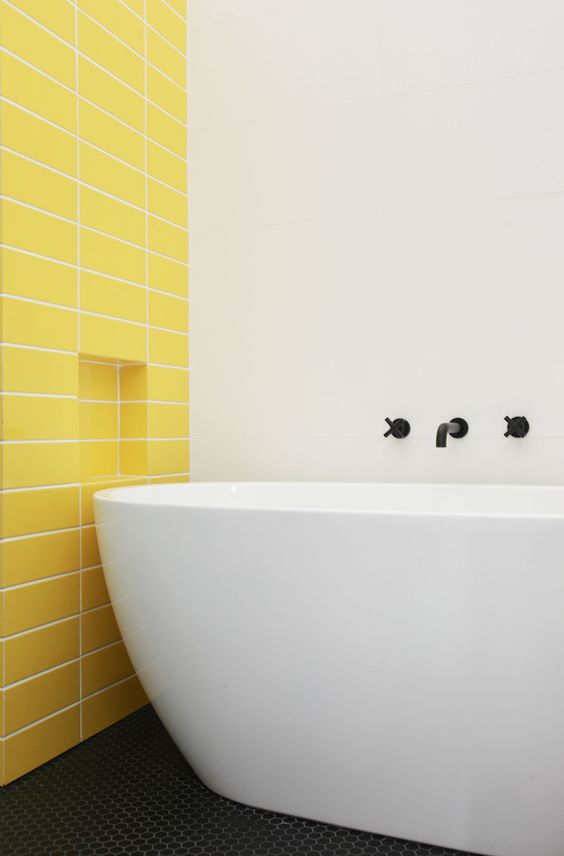 a minimalist bathroom with a statement yellow tile wall and a neutral and sleek bathtub