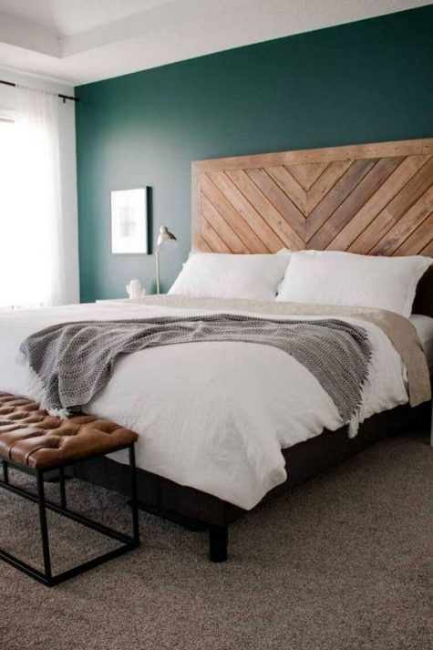 a wooden headboard done in a chevron pattern and a leather bench add texture to the bedroom