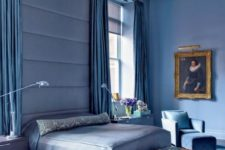 25 an oversized blue upholstered headboard coming up to the ceiling softens the space visually and makes it more modern