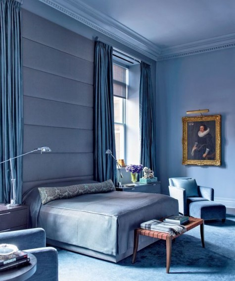 an oversized blue upholstered headboard coming up to the ceiling softens the space visually and makes it more modern