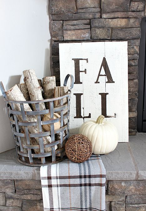 a metal basket with branches, a plaid blanket, a vine ball, a white pumpkin and a sign