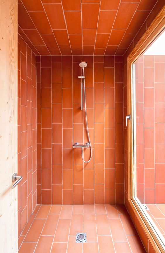 a shower space accented with brigth coral tiles to make it stand out in the bathroom