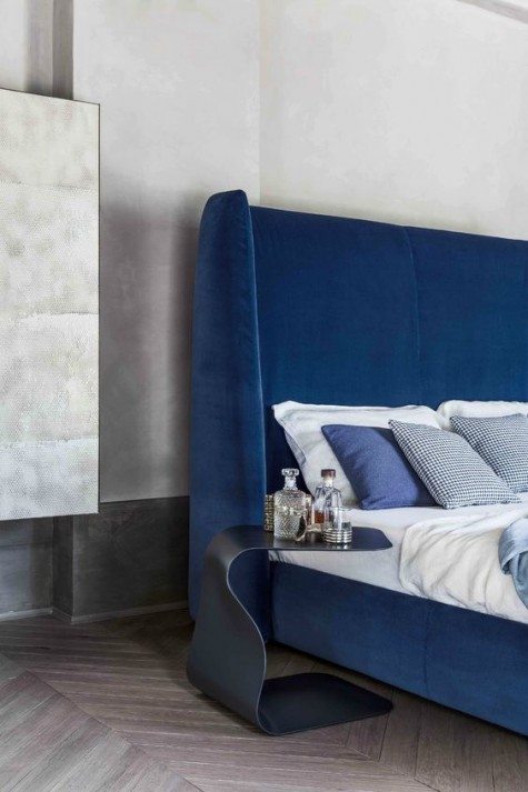 an ultra modern electric blue wingback headboard accented with a catchy curved nightstand