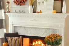 27 a fall fireplace with candles, bright blooms, pumpkins, pinecones, leaves and a candle lantern