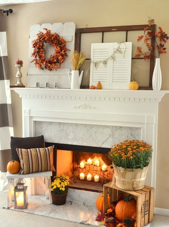 a fall fireplace with candles, bright blooms, pumpkins, pinecones, leaves and a candle lantern