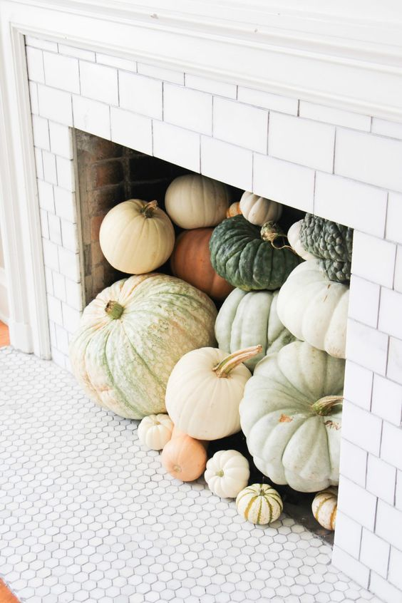 a non working fireplace fully filled with heirloom pumpkins is an amazing fall idea