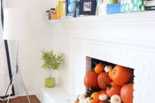 29 a non-working fireplace filled with various pumpkins for the fall and coming Halloween