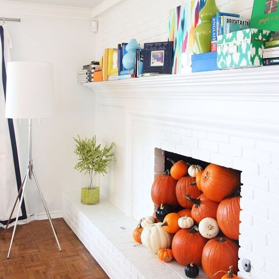 a non-working fireplace filled with various pumpkins for the fall and coming Halloween