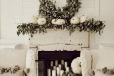 30 a mantel styled with greenery, white pumpkins and a large wreath of wine and greenery