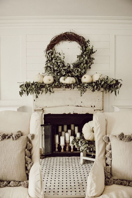 a mantel styled with greenery, white pumpkins and a large wreath of wine and greenery