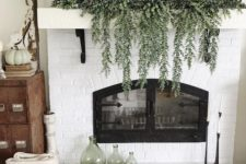 31 a mantel decorated with cascading greenery, three white pumpkins and a dough bowl