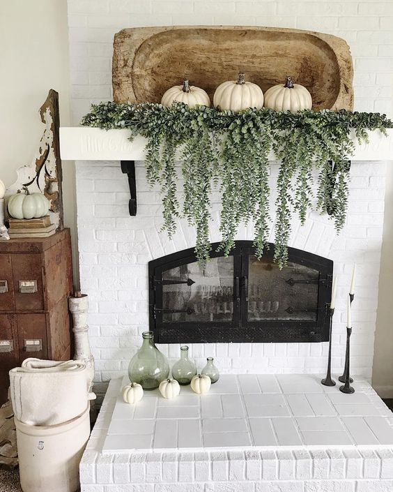 a mantel decorated with cascading greenery, three white pumpkins and a dough bowl
