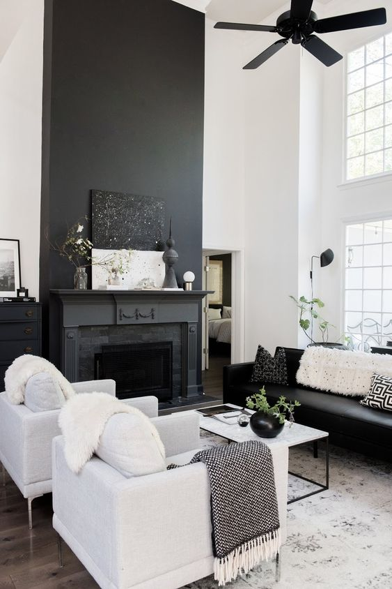 a Nordic living room with a black fireplace, black and white furniture, a black fan and a white coffee table