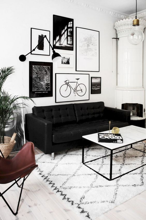 a Nordic living room with a gallery wall, a white stove, a printed rug and a black leather sofa plus greenery