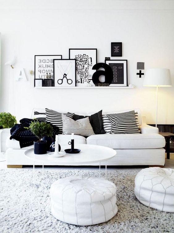 a Nordic living room with a gallery wall on a ledge, a white sofa, leather ottomans and a pack of striped pillows