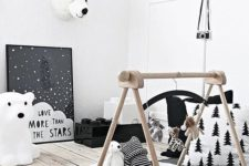 a Nordic nursery with a baby gym, artworks, a rug and toy bear heads to make it more atmospheric