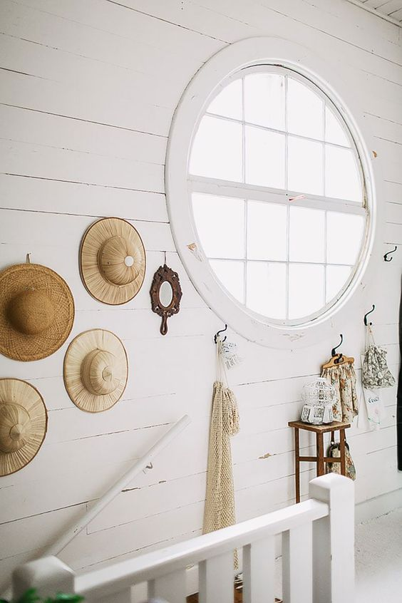 a Nordic staricase space done with white paint and a large porthole window that allows much light inside