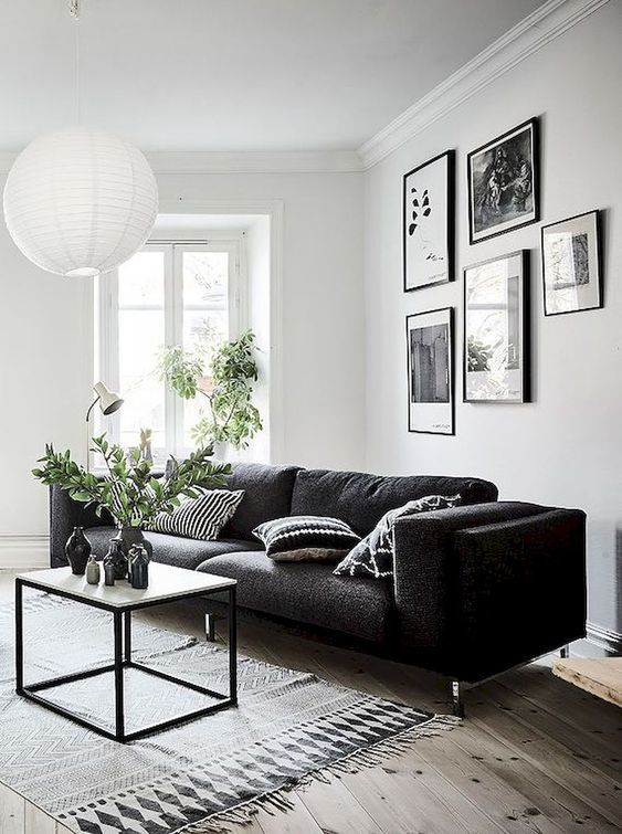 a Scandinavian living room with a black sofa, a small coffee table and a pendant lamp and a gallery wall