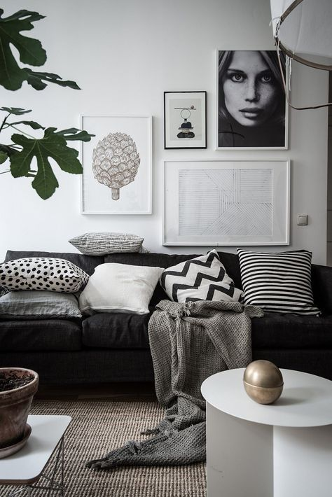 a Scandinavian living room with a gallery wall, greenery and a coffee table in white plus a gold touch