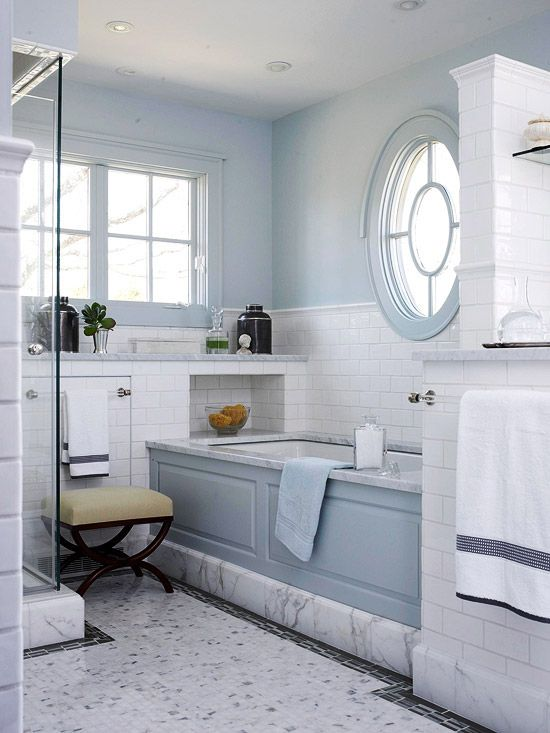 a beautiful light blue and white bathroom with marble and subway tiles, a porthole window nd a usual one