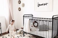 a black and white nursery with a printed rug, a black bed, a bead chandelier and a simple artwork