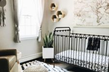 a black and white nursery with a printed rug, hexagon shelves and a map plus a neutral chair and footrest