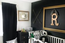 a black and white room with an accent wall, a black dresser and curtains and a striped rug is a cool and bold space