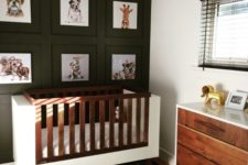 a black and white space with a black statement wall, a modern crib and dresser, black shades and a buffalo check rug