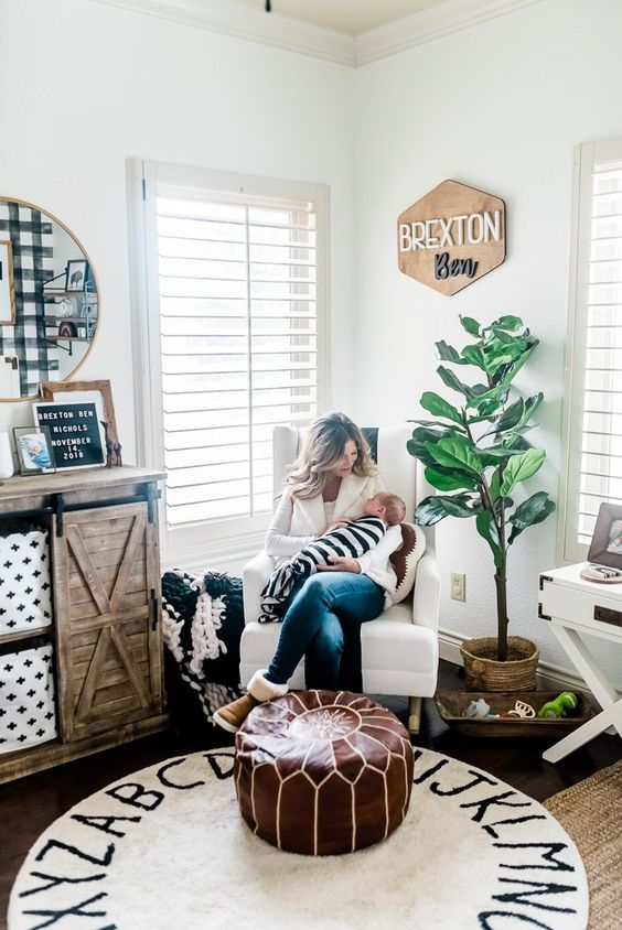 a boho farmhouse nursery with a leather ottoman, a printed rug, a reclaimed wood dresser and a potted plant