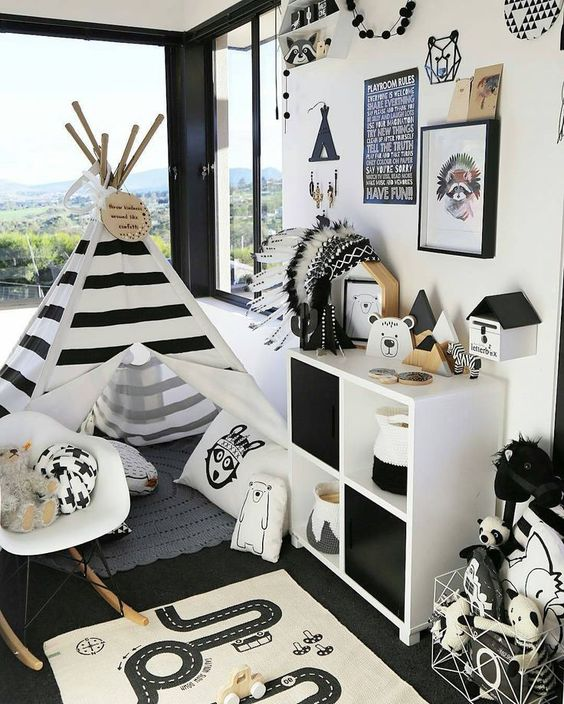 a bold adventuruous nursery with a striped teepee, a dresser, a gallery wall and a play rug on the floor