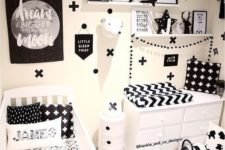 a bold monochromatic nursery with open shelving, a changing table and a crib plus lots of prints everywhere