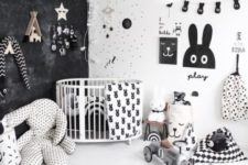 a catchy and bold nurseyr with a black wall, some prints, a gallery wall of artworks and garlands and lot sof toys