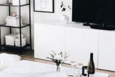 a chic Nordic living room with white furniture, some touches of black and a gallery wall, prints are incorporated with a rug