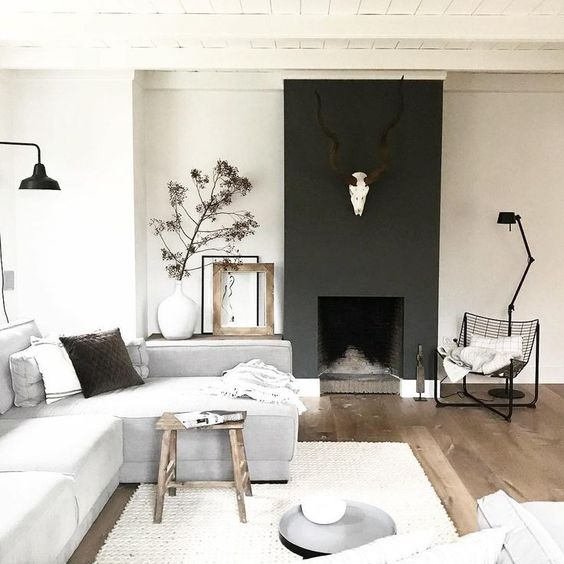 a chic Scandinavian living room with a blakc fireplac,e neutral furniture, wooden touches and greenery here and there