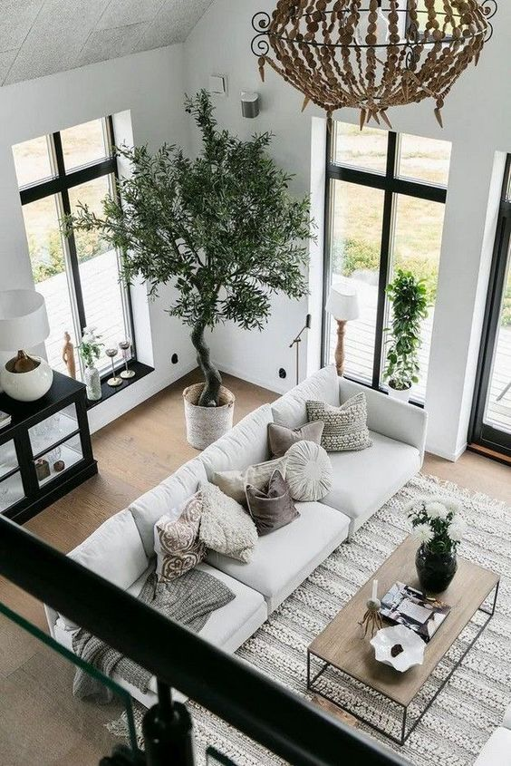 a chic black and white living room diluted with some natural wood and a crochet rug plus greenery for a welcoming feel