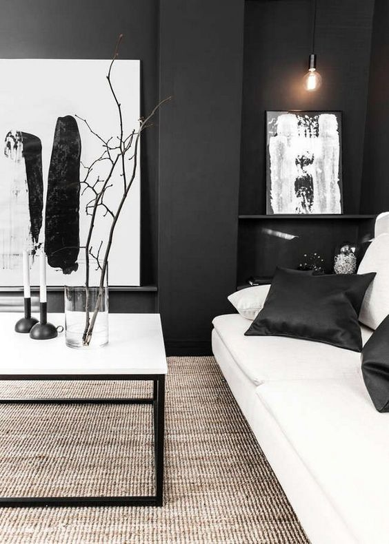 a chic black and white living room with graphic artworks, a white sofa, a coffee table and a textural rug