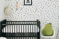 a chic black and white nursery with a black crib, a spotted wall, a printed rug and a single green pear pillow for a touch of color