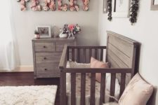 a chic farmhouse meets vintage and boho nursery with reclaimed wooden furniture, a floral name, fluffy rugs and artworks