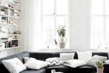 a chic living room with shelves, a black sectional, a couple of catchy coffee tables and a jute rug