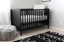 a chic nursery with a black crib, a printed rug, wooden shelves and a pretty artwork for a simple andd cozy space