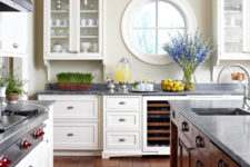 a chic rustic kitchen with white and stained furniture, a porthole window and lots of greenery and blooms