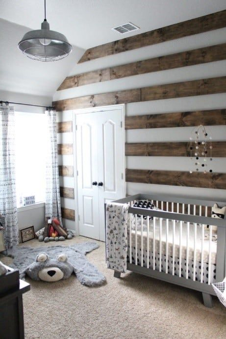 a chic woodland nursery with a striped stained wood wall, layered rugs, a grey vintage crib, a pendant lamp and lace curtains