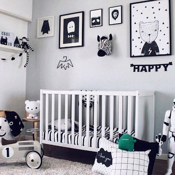 a classy Scandinavian nursery with a gallery wall, pillows, a white crib and shelves for storage