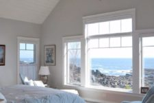 a coastal bedroom done in light blues and white, with a large window and a tiny porthole to embrace the location