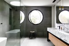 a contemporary bathroom with concrete tiles, a marble vanity, a round pivot window for a modern feel
