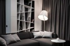 a contemporary black and white living room with a built-in geometric shelf, a sectional sofa and a black ottoman